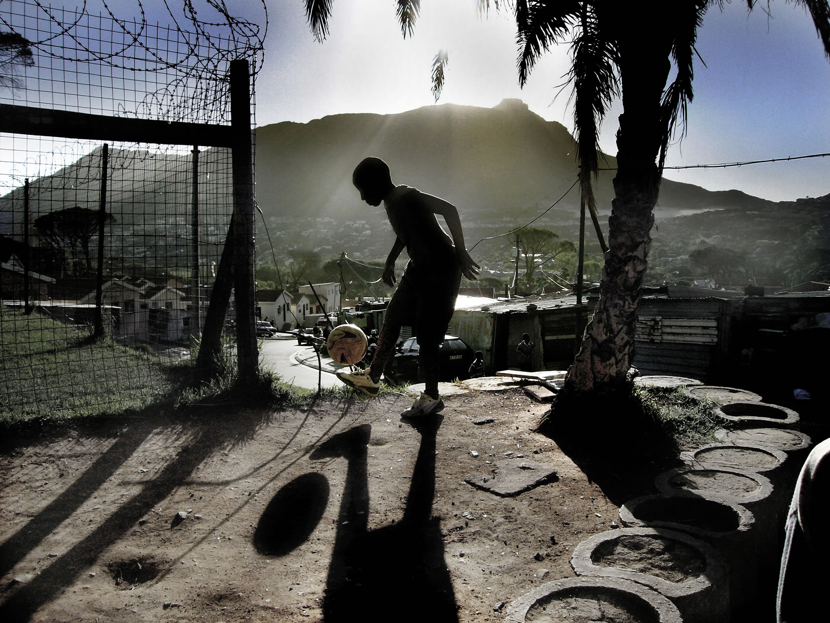 youngster plays football in south Africa township